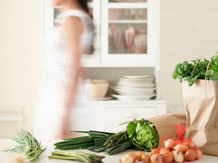 busy blurred woman walking passed vegetables on the counter