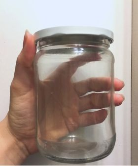 hand holding empty jar. Remove the label from glass jars so you can reuse them