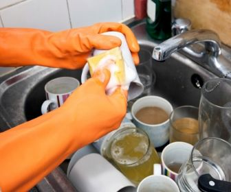 washing dirty mugs in sink