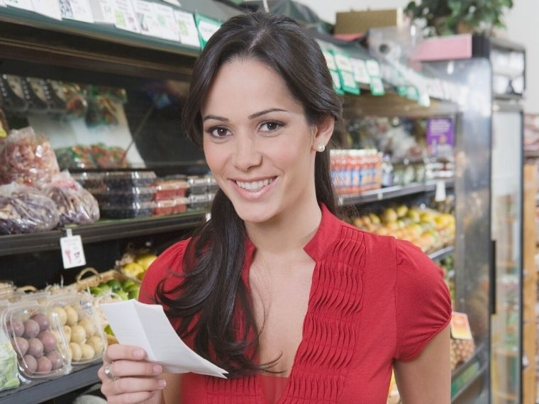 Woman in Grocery store looking at Master Grocery List