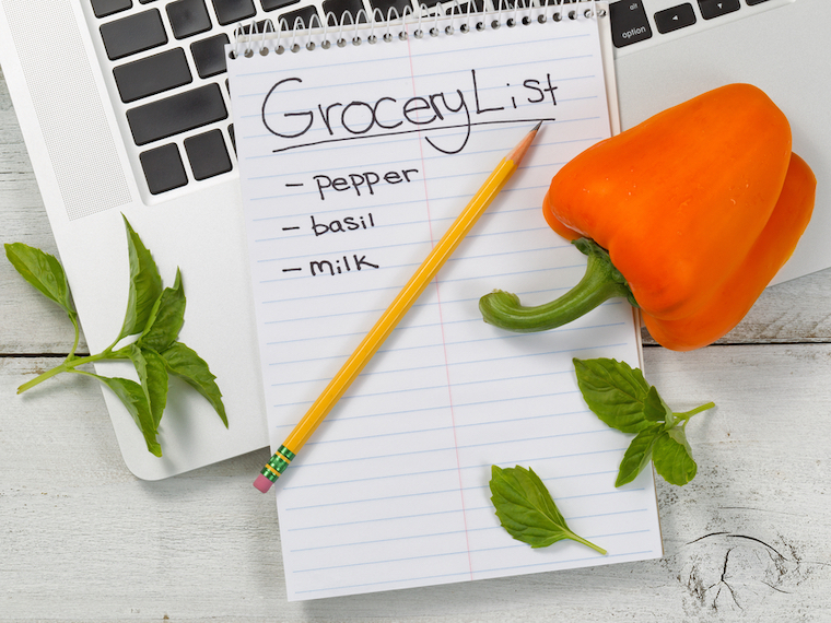 grocery list for Amazon notepad, pencil, bell pepper, leaves, laptop flatlay